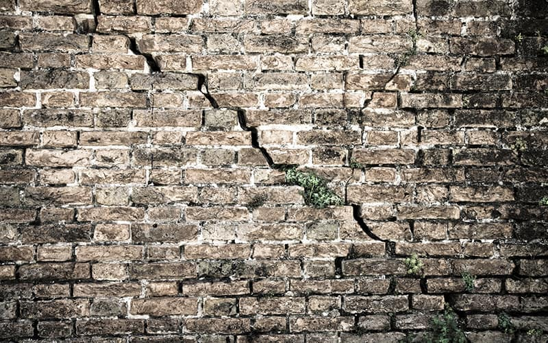 a brick wall showing significant subsidence cracks requiring insurance claim